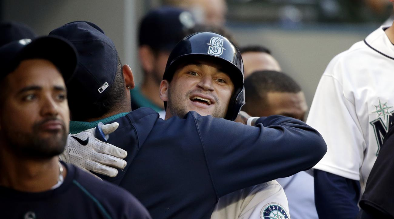 Seattle Mariners' Mike Zunino is embraced in the dugout after his home run against the Arizona Diamondbacks in the third inning of a baseball game, Tuesday, July 28, 2015, in Seattle. (AP Photo/Elaine Thompson)