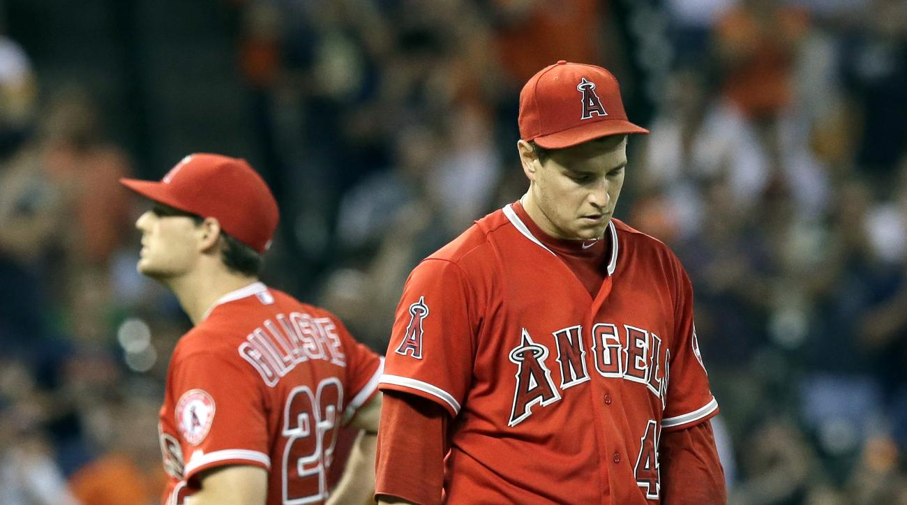 Los Angeles Angels starting pitcher Garrett Richards, right, heads back to the mound as third baseman Conor Gillaspie (22) goes back to third after Houston Astros' Jose Altuve hit an RBI-single in the fifth inning of a baseball game Wednesday, July 29, 20