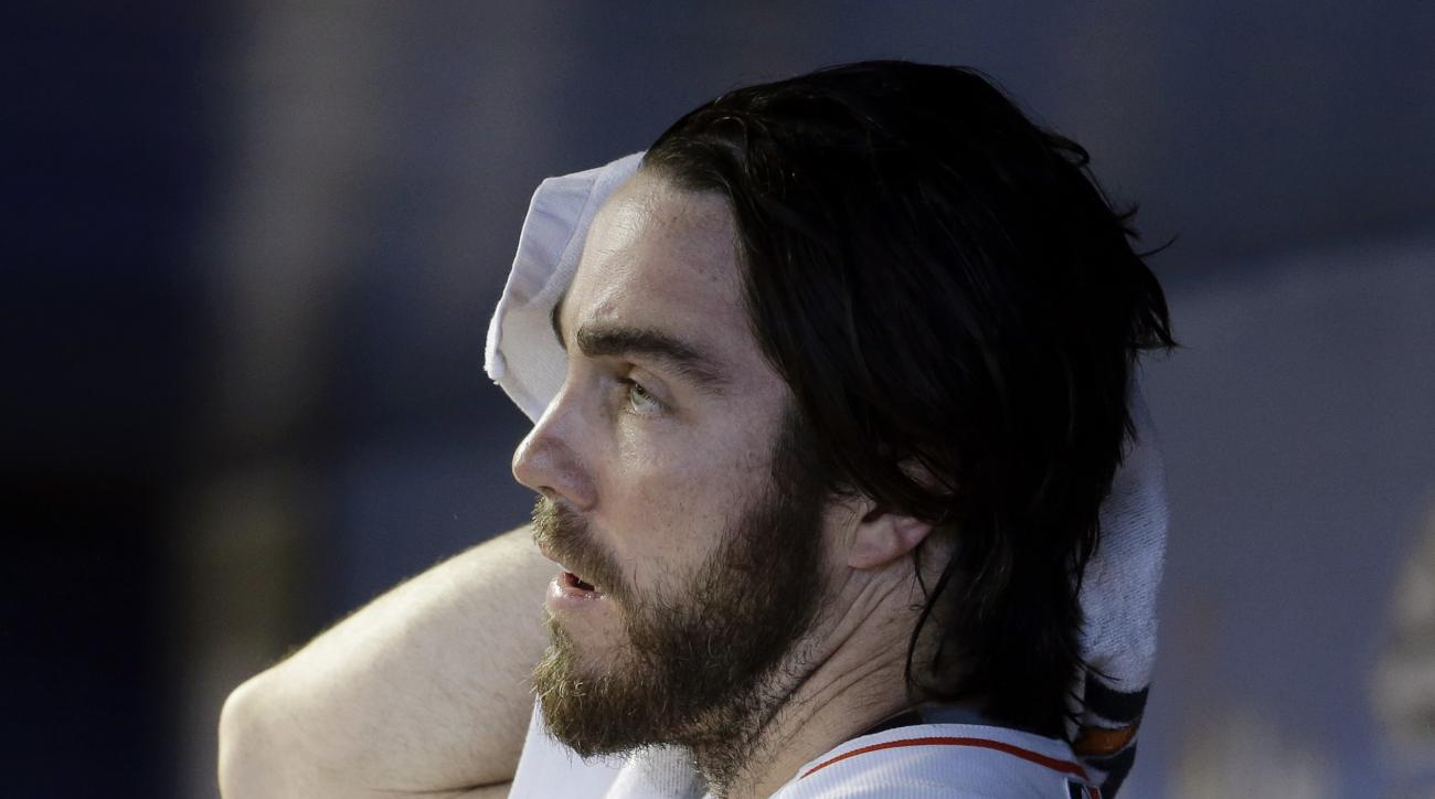 Miami Marlins starting pitcher Dan Haren wipes his head with a towel after throwing in the first inning of a baseball game against the Washington Nationals, Thursday, July 30, 2015, in Miami. (AP Photo/Lynne Sladky)