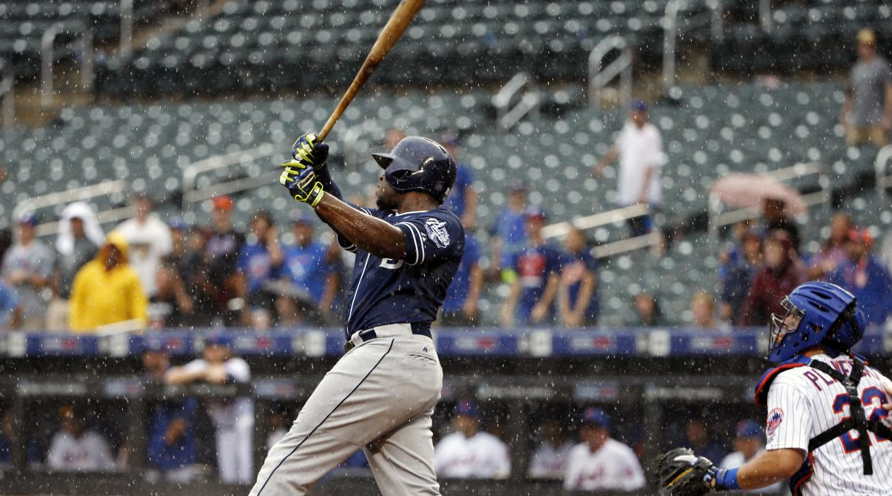 As rain falls, San Diego Padres' Justin Upton, left, hits a ninth-inning three-run home run off New York Mets relief pitcher Jeurys Familia in a baseball game in New York, Thursday, July 30, 2015. Mets catcher Kevin Plawecki (22) watches, right. (AP Photo