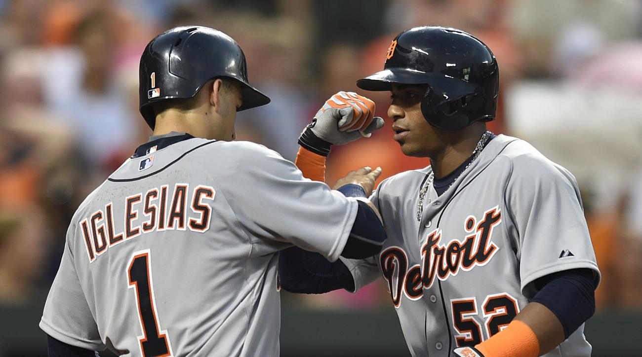 Detroit Tigers' Yoenois Cespedes, right, is congratulated by teammate Jose Iglesias after hitting a two-run home run against the Baltimore Orioles in the fourth inning of a baseball game, Thursday, July 30, 2015, in Baltimore. (AP Photo/Gail Burton)