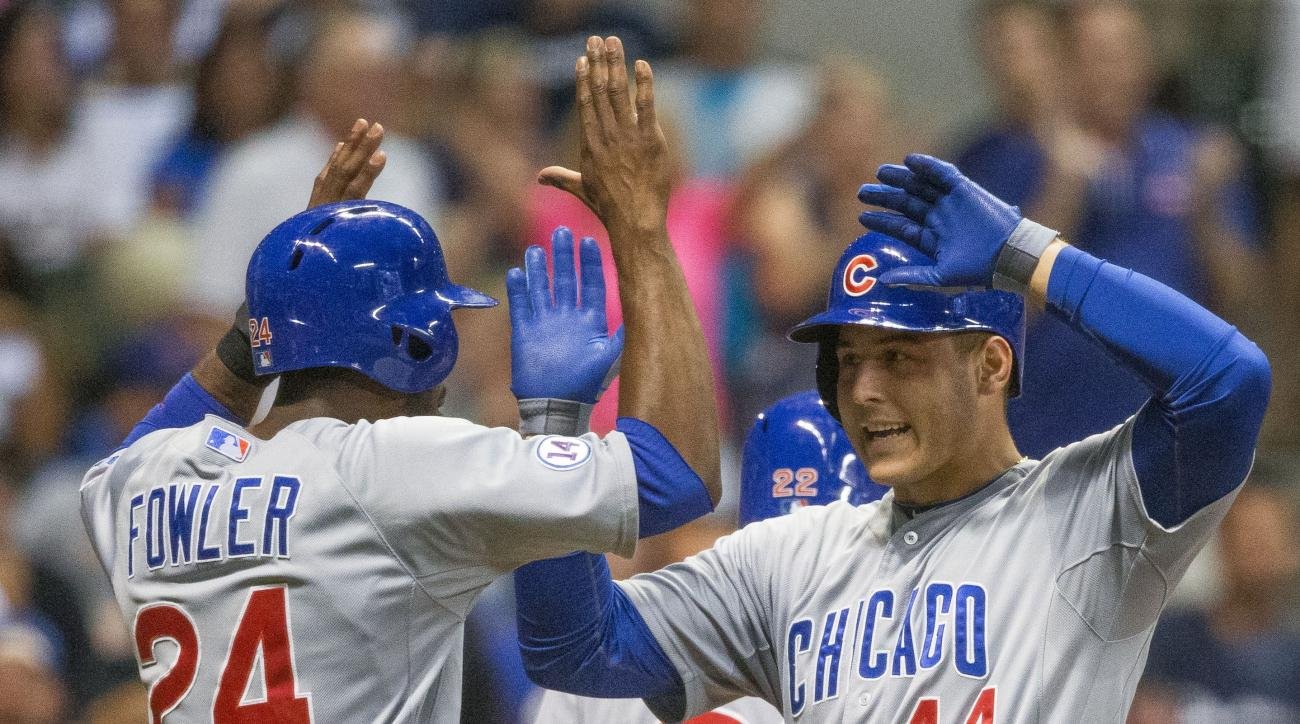 Chicago Cubs' Anthony Rizzo  gets a high five from teammate Dexter Fowler after hitting a three run home run off Milwaukee Brewers' Jeremy Jeffress during the eighth inning of a baseball game Thursday, July 30, 2015, in Milwaukee. (AP Photo/Tom Lynn)