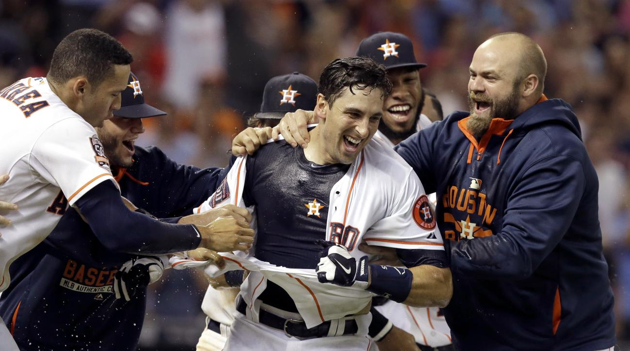 Houston Astros rip the jersey off Jason Castro, center, after he hit a walkoff three-run home run to defeat the Los Angeles Angels 3-0 in the ninth inning of a baseball game Thursday, July 30, 2015, in Houston. (AP Photo/Pat Sullivan)