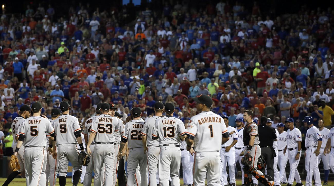 The San Francisco Giants and the Texas Rangers meet on the field after a heated exchange between Giant's Madison Bumgarner and members of the Rangers in the fourth inning of a baseball game Friday, July 31, 2015, in Arlington, Texas. (AP Photo/Tony Gutier