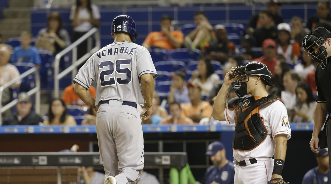 San Diego Padres' Will Venable (25) scores on a walk by Yonder Alonso with the bases loaded as Miami Marlins catcher J.T. Realmuto looks on in the eleventh inning of a baseball game, Friday, July 31, 2015, in Miami. The Padres defeated the Marlins 8-3 in