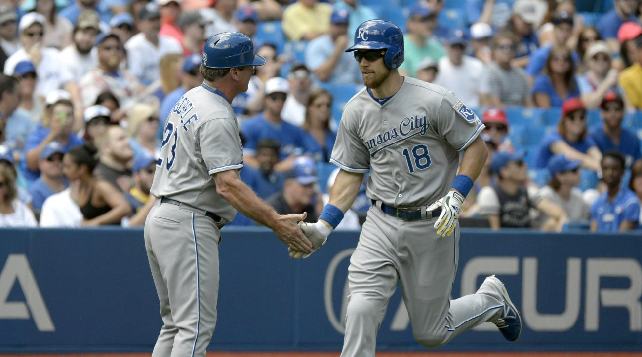 Kansas City Royals' Ben Zobrist, right, slaps hands with Royals' third base coach Mike Jirschele after hitting a solo home run against the Toronto Blue Jays during the first inning of a baseball game Saturday, Aug. 1, 2015, in Toronto. (Jon Blacker /The C