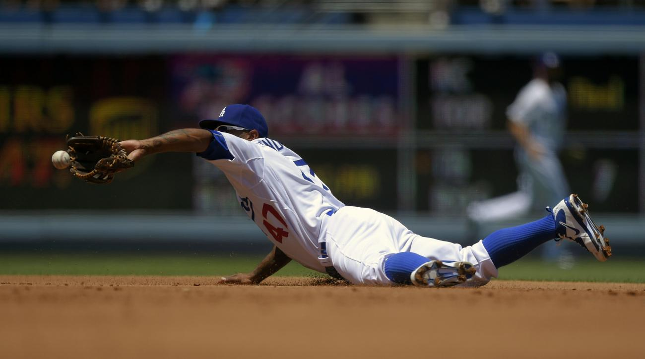 Los Angeles Dodgers second baseman Howie Kendrick tosses the ball to second to force out Los Angeles Angels' Albert Pujols after fielding a ball hit by Erick Aybar during the second inning of a baseball game, Saturday, Aug. 1, 2015, in Los Angeles. Aybar