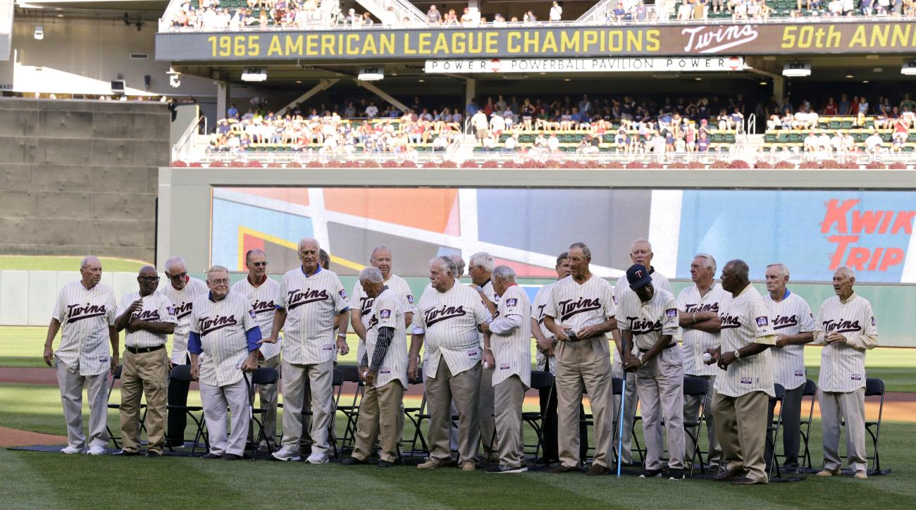 Members of the 1965 Minnesota Twins gather on the field during a 1965 American League Championship Anniversary celebration prior to the Twins baseball game against the Seattle Mariners in Minneapolis, Saturday, Aug. 1, 2015. (AP Photo/Ann Heisenfelt)