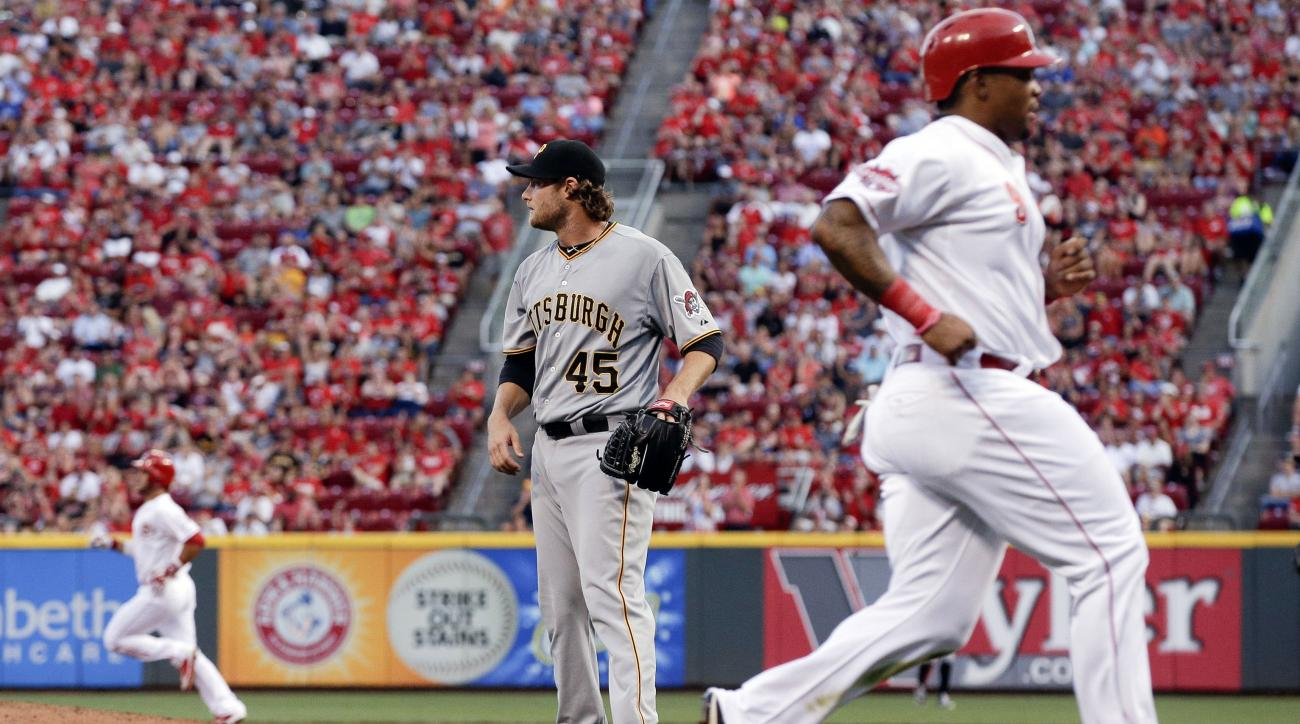 Pittsburgh Pirates starting pitcher Gerrit Cole stands in the infield as Cincinnati Reds' Marlon Byrd, right, runs home off a double hit by Eugenio Suarez, left, in the fourth inning of a baseball game, Saturday, Aug. 1, 2015, in Cincinnati. (AP Photo/Joh