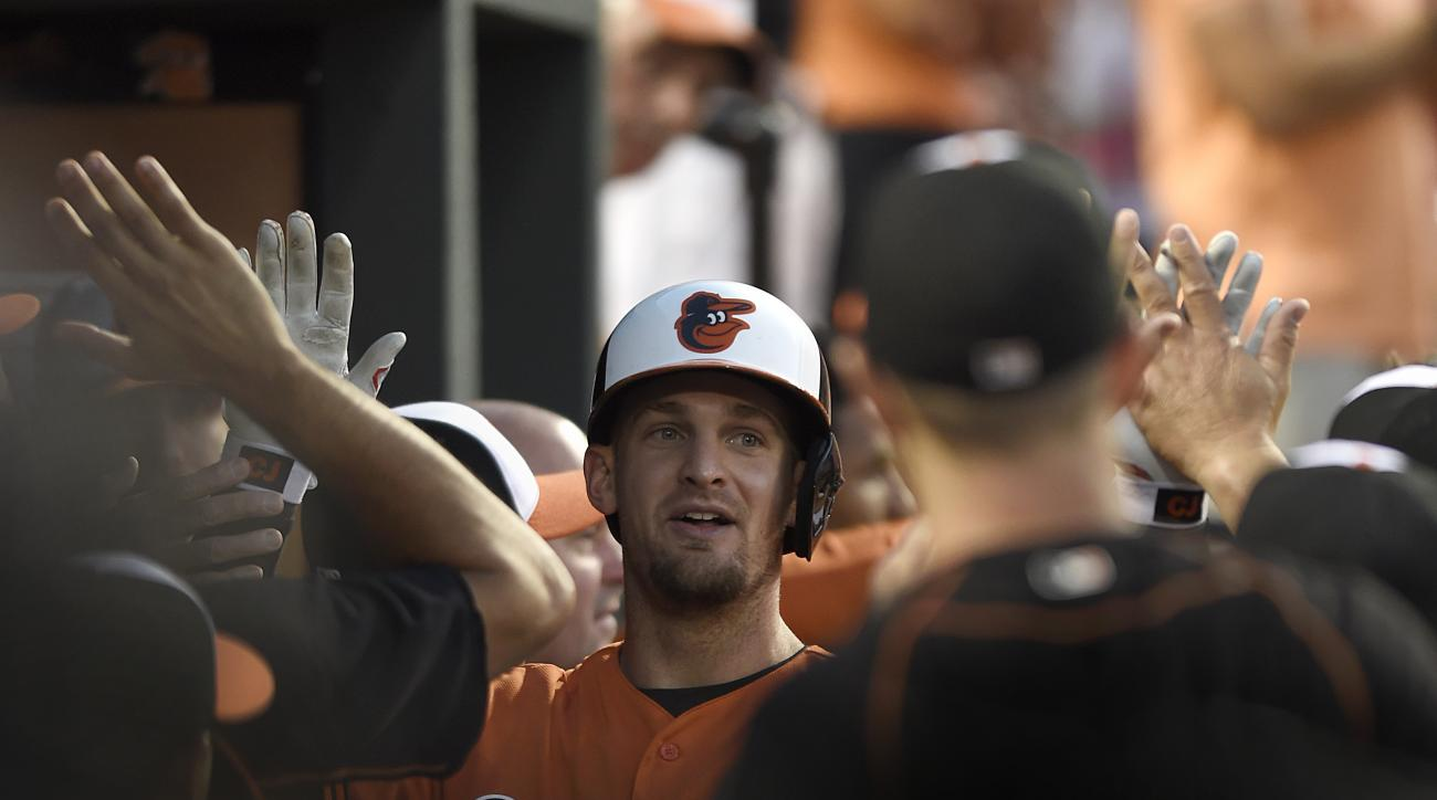Baltimore Orioles' Caleb Joseph is congratulated in the dugout after hitting a two-run home run against the Detroit Tigers during the fourth inning of a baseball game, Saturday, Aug. 1, 2015, in Baltimore.(AP Photo/Gail Burton)