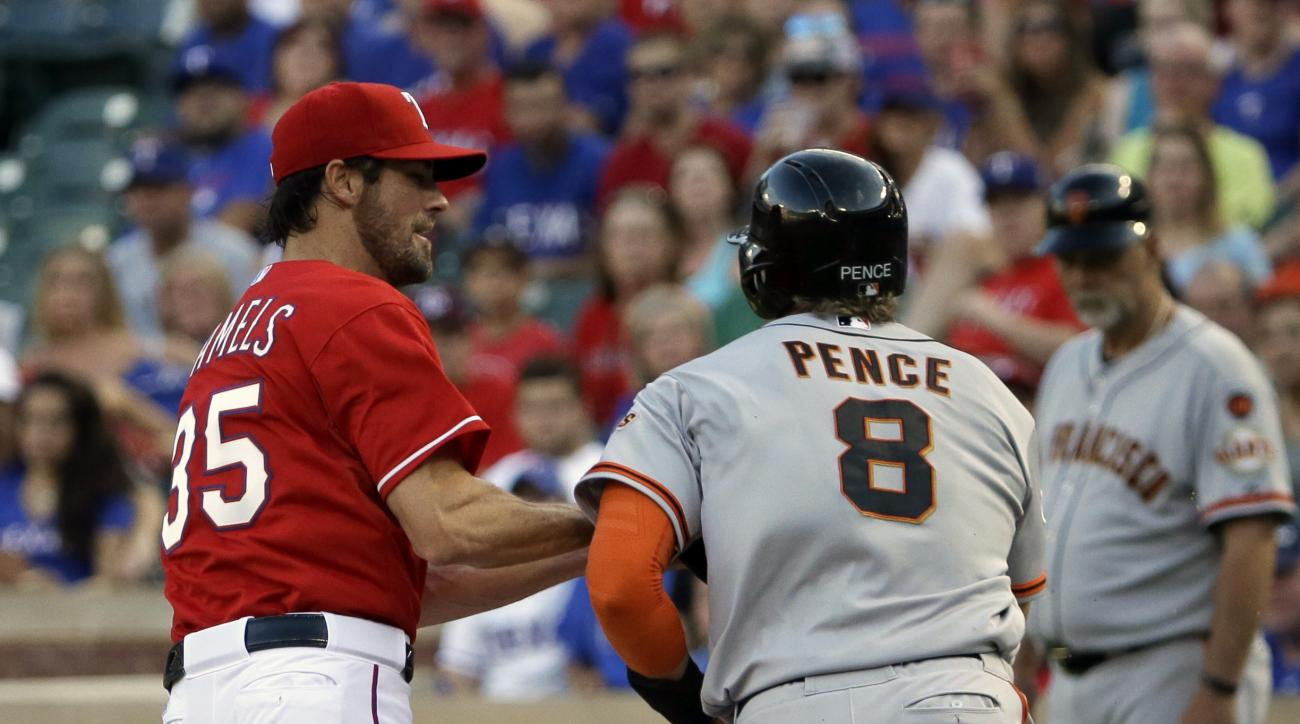 Texas Rangers starting pitcher Cole Hamels (35) tags out San Francisco Giants' Hunter Pence (8) as they run toward first base during the second inning of a baseball game in Arlington, Texas, Saturday, Aug. 1, 2015. (AP Photo/LM Otero)