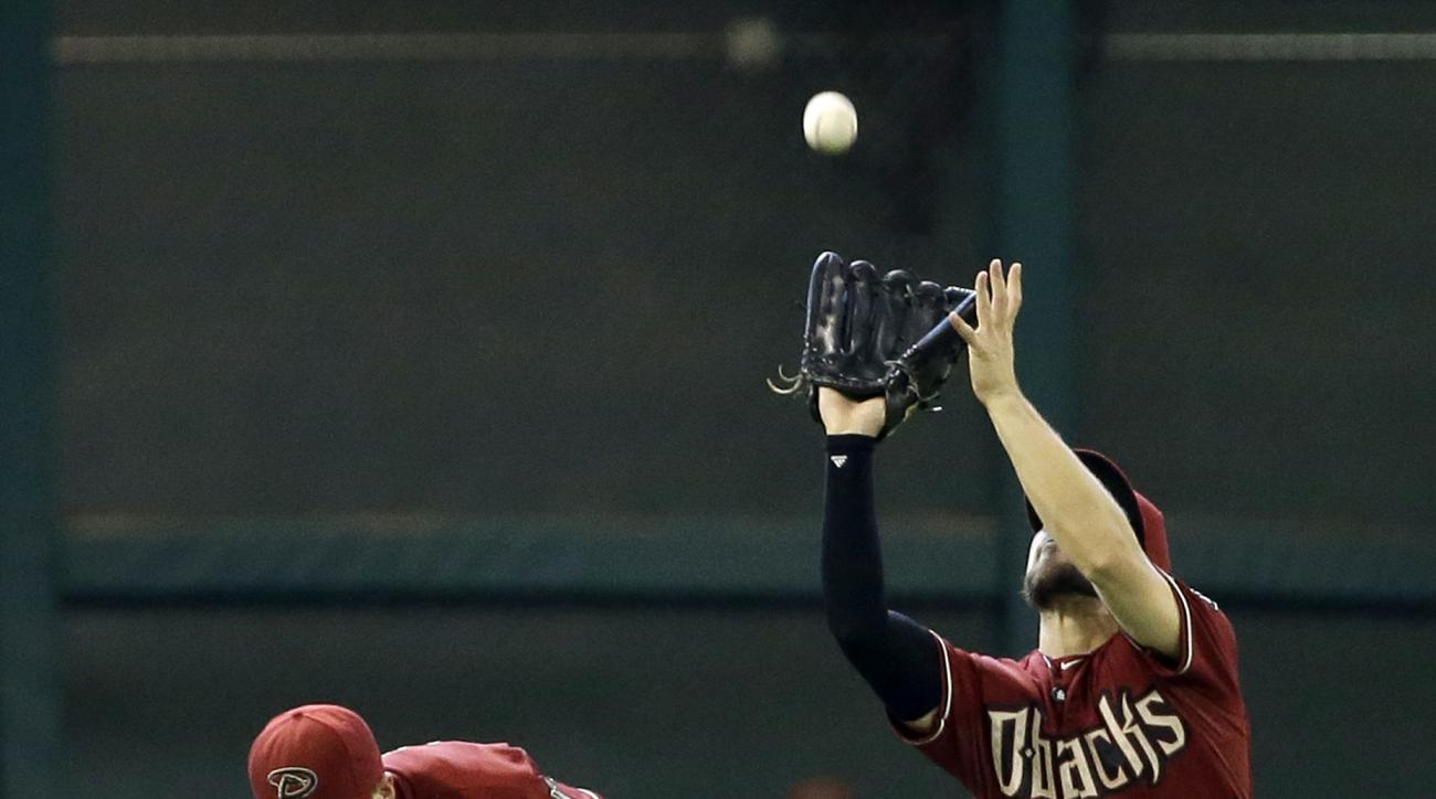 Arizona Diamondbacks center fielder Ender Inciarte, right, catches a fly ball hit by Houston Astros' Chris Carter as Nick Ahmed, left, ducks out of the way during the seventh inning of a baseball game Sunday, Aug. 2, 2015, in Houston. (AP Photo/David J. P