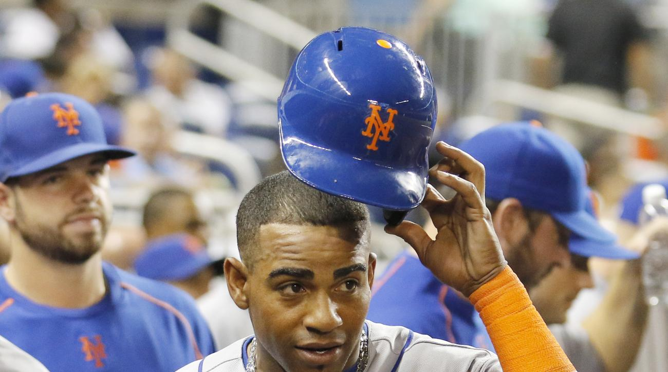 New York Mets hitter Yoenis Cespedes walks in the dugout after he scored on a double by teammate Wilmer Flores in the fifth inning against the Miami Marlins during a baseball game in Miami, Monday Aug. 3, 2015. Cespedes got on base with a two-run double.
