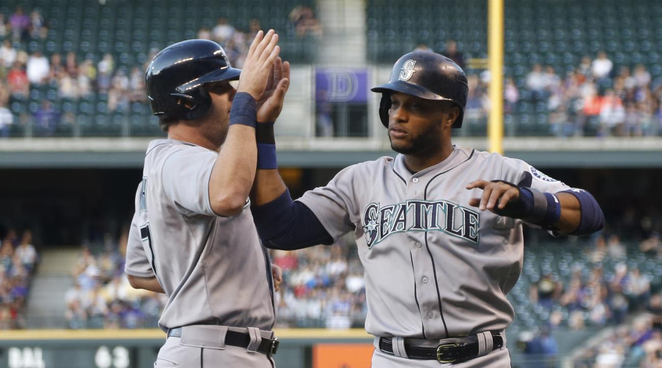 Seattle Mariners' Seth Smith, left, is congratulated by Robinson Cano after they scored on a double by Jesus Montero against the Colorado Rockies in the first inning of an inter league baseball game Monday, Aug. 3, 2015, in Denver. (AP Photo/David Zalubow