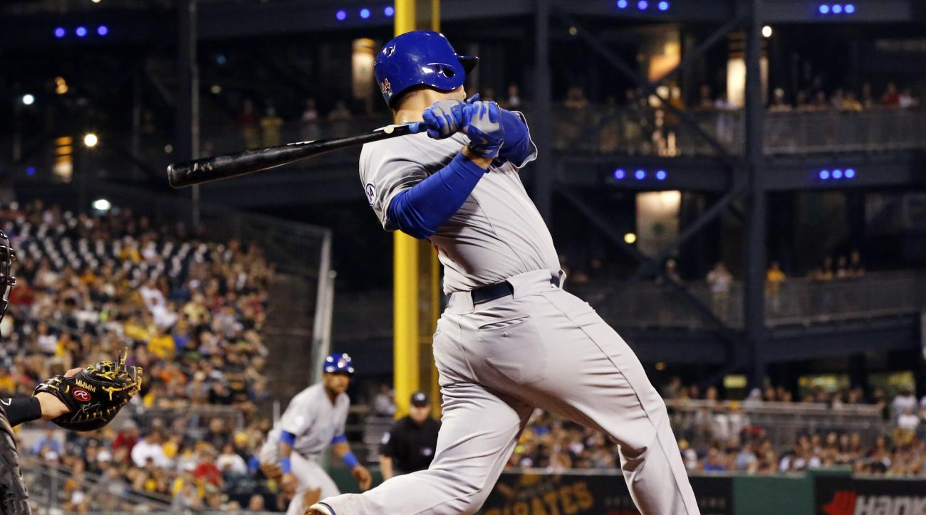Chicago Cubs' Anthony Rizzo, center,  singles off Pittsburgh Pirates relief pitcher Joe Blanton, driving in teammate Addison Russell, left, from third during the third inning of a baseball game in Pittsburgh, Monday, Aug. 3, 2015. (AP Photo/Gene J. Puskar