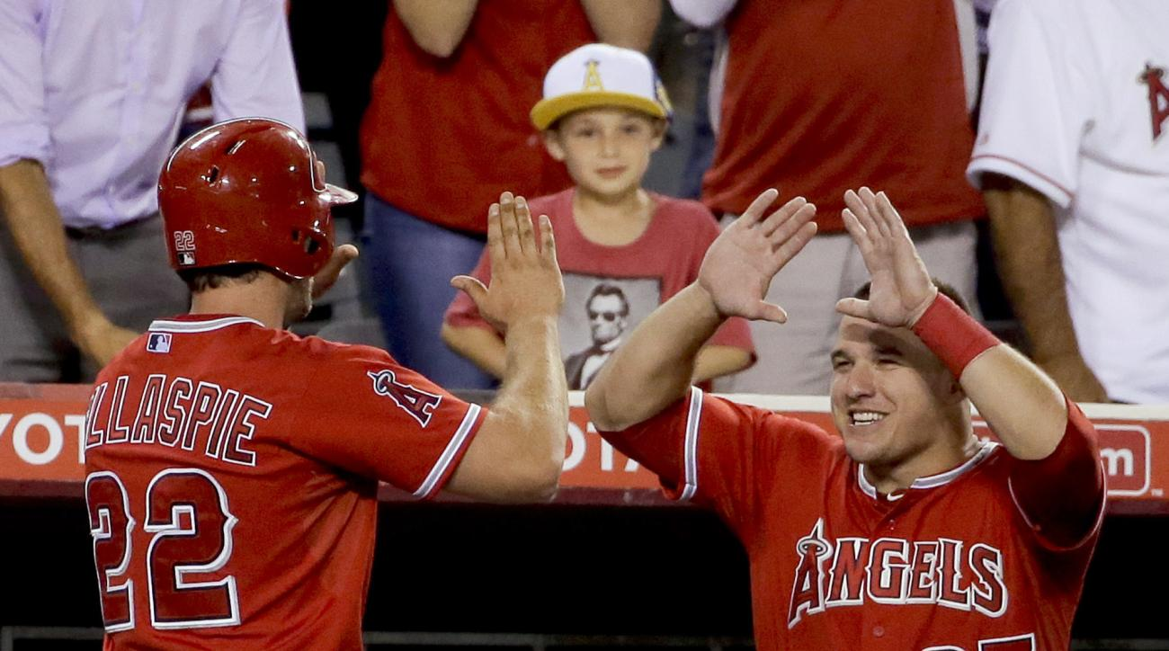 Los Angeles Angels' Conor Gillaspie, left, celebrates after a two run home run in the dugout with Mike Trout during the sixth inning of a baseball game against the Cleveland Indians in Anaheim, Calif., Monday, Aug. 3, 2015. (AP Photo/Chris Carlson)