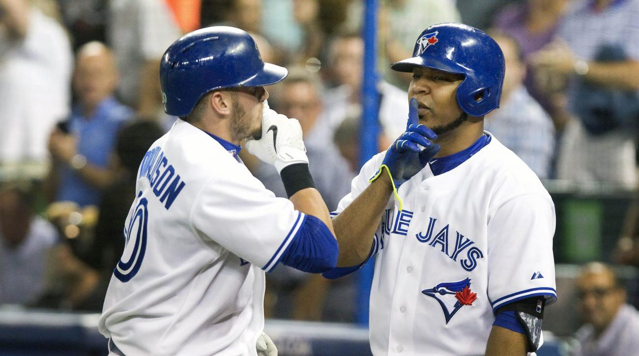 Toronto Blue Jays' Edwin Encarnacion, right, greets teammate Josh Donaldson with a whisper gesture after Donaldson hit a home run against the Minnesota Twins during the first inning of a baseball game, Tuesday, Aug. 4, 2015 in Toronto.  (Fred Thornhill/Th
