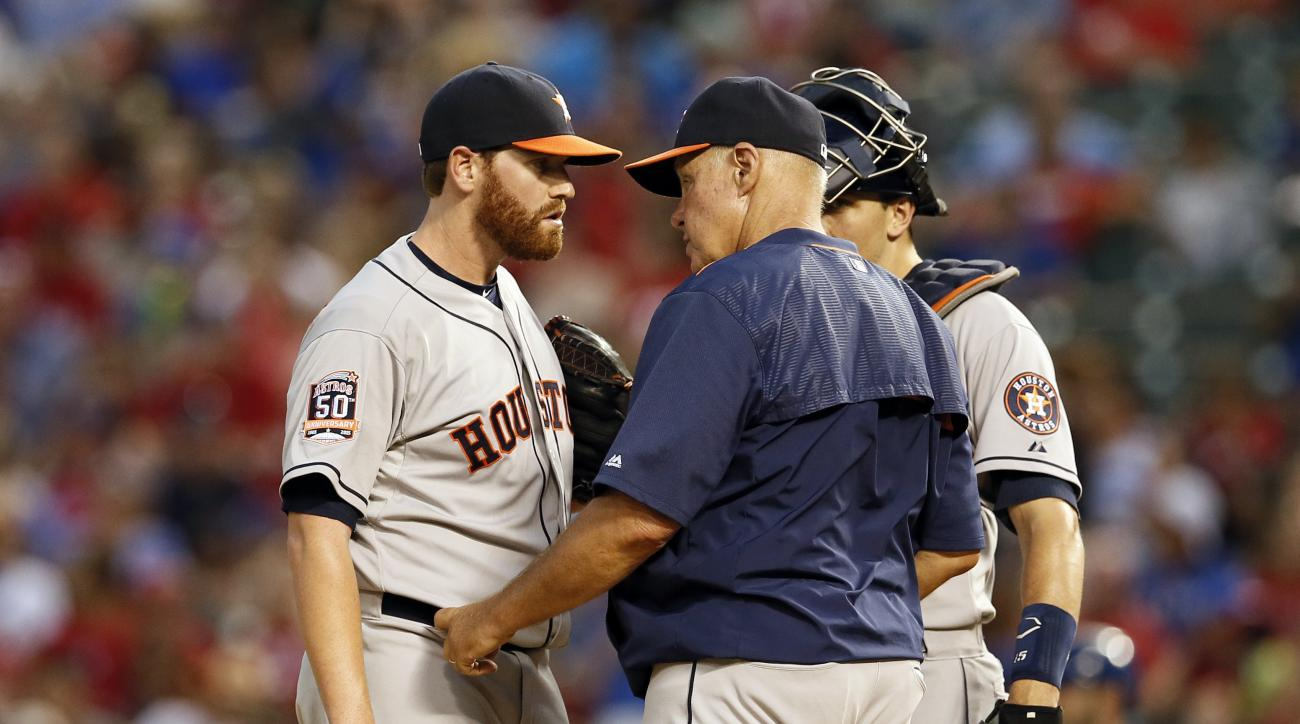 Houston Astros starting pitcher Dan Straily talks with pitching coach Brent Strom, center, as catcher Jason Castro listens in the fourth inning of a baseball game against the Texas Rangers Tuesday, Aug. 4, 2015, in Arlington, Texas. (AP Photo/Tony Gutierr