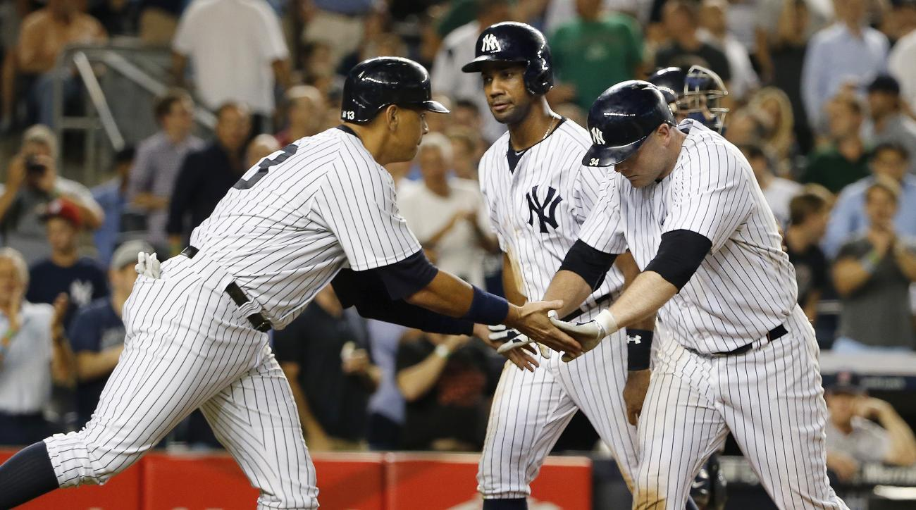 New York Yankees' Alex Rodriguez, left, celebrates with Brian McCann after Rodriguez and Chris Young, center, scored on McCann's seventh-inning home run in a baseball game against the Boston Red Sox at Yankee Stadium in New York, Tuesday, Aug. 4, 2015.  (