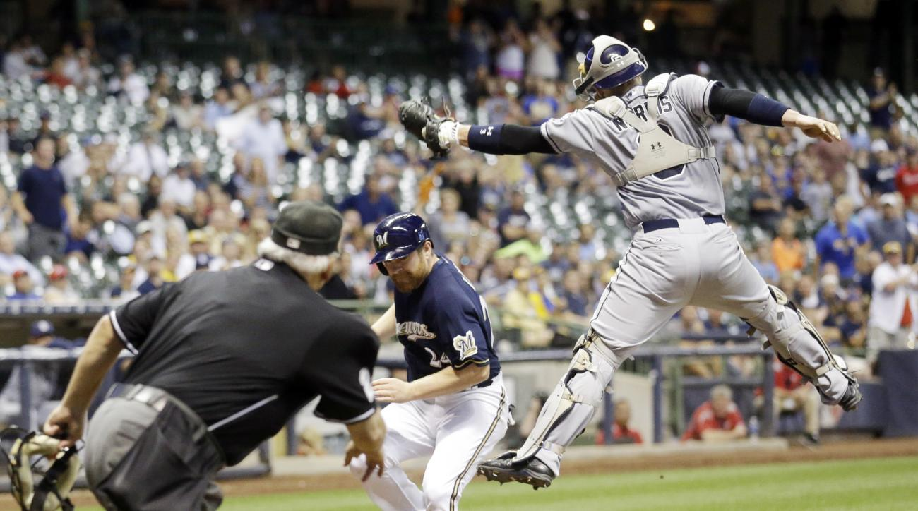 Milwaukee Brewers' Adam Lind scores safely past a leaping San Diego Padres catcher Derek Norris during the seventh inning of a baseball game Tuesday, Aug. 4, 2015, in Milwaukee. (AP Photo/Morry Gash)