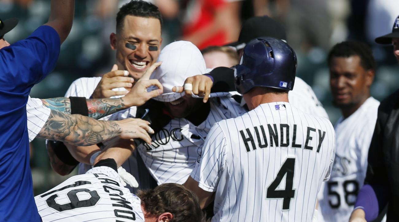 Colorado Rockies' Michael McKenry, center, has his jersey pulled over his head by a teammate as Charlie Blackmon, front left, and Nick Hundley join in the celebration after McKenry's two-run home run against the Seattle Mariners during the 11th inning of