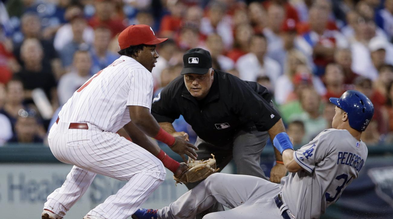 Philadelphia Phillies third baseman Maikel Franco, left, tags out Los Angeles Dodgers' Joc Pederson, right, after Pederson tried to advance to third base on a single by Alberto Callaspo during the fourth inning of a baseball game, Wednesday, Aug. 5, 2015,