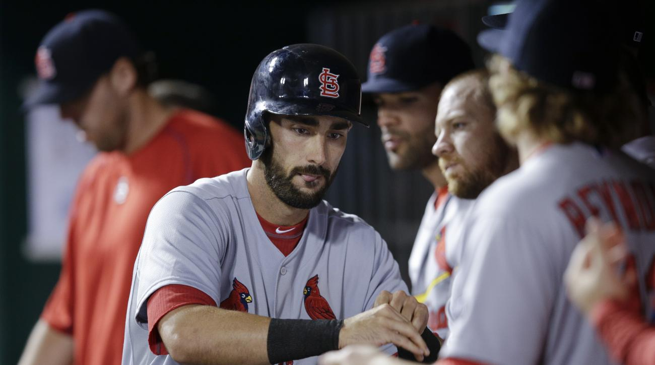 St. Louis Cardinals' Matt Carpenter celebrates in the dugout after hitting a game-tying solo home run off Cincinnati Reds relief pitcher J.J. Hoover during the eighth inning of a baseball game, Wednesday, Aug. 5, 2015, in Cincinnati. (AP Photo/John Minchi