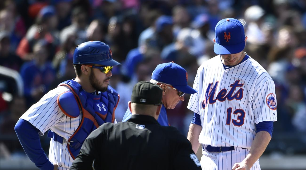 New York Mets catcher Travis d'Arnaud, left, manager Terry Collins, top center, and home plate umpire Sean Barber, bottom center, examine relief pitcher Jerry Blevins' (13) injured left forearm in the seventh inning of a baseball game against the Miami Ma