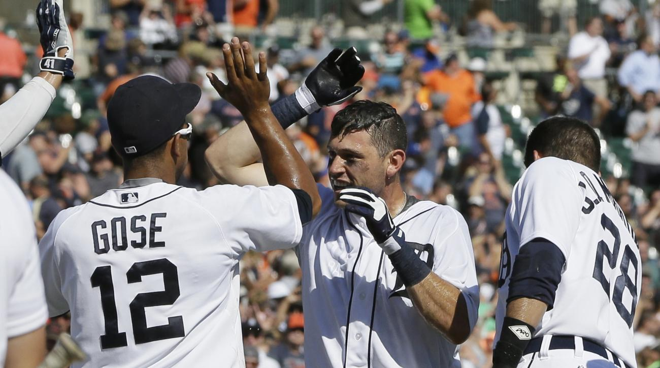 Detroit Tigers' Ian Kinsler, center, is congratulated by teammate Anthony Gose and J.D. Martinez after his two-run walk-off home run off Kansas City Royals relief pitcher Ryan Madson during the ninth inning of a baseball game, Thursday, Aug. 6, 2015, in D