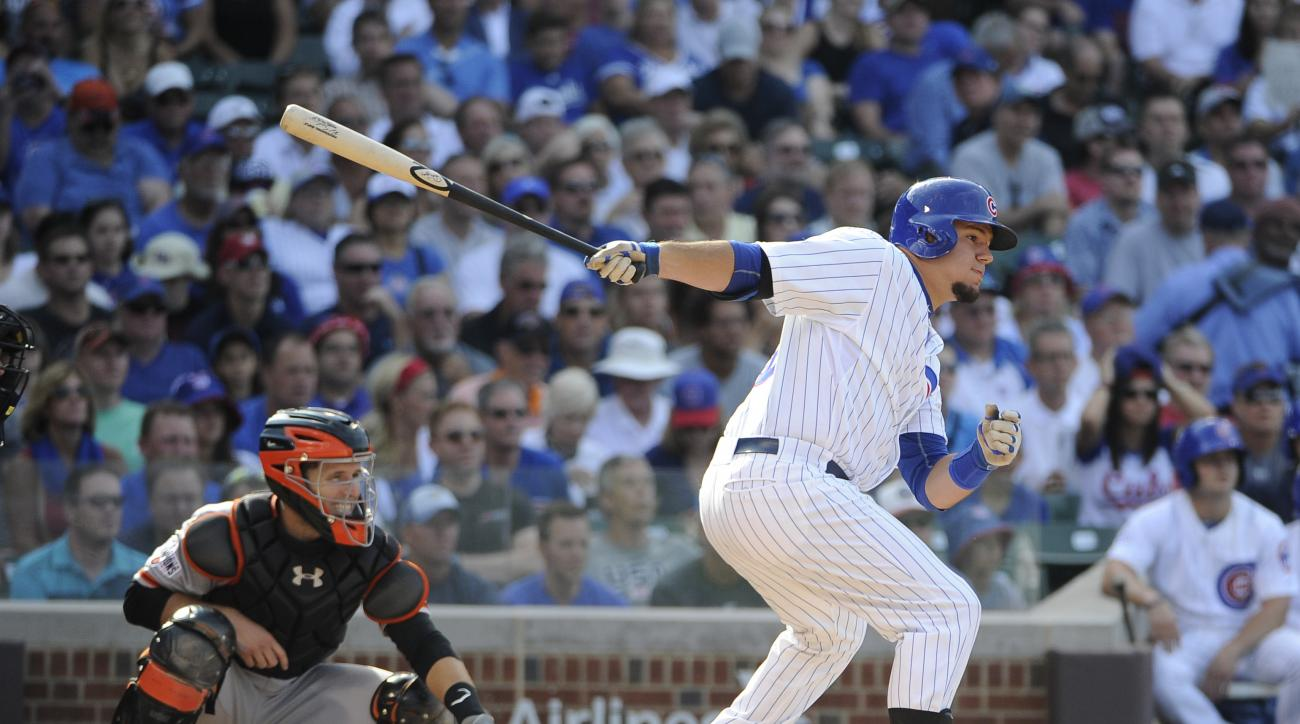 Chicago Cubs' Kyle Schwarber, right, hits a two-RBI single against the San Francisco Giants during the fifth inning of a baseball game, Friday, Aug. 7, 2015, in Chicago. (AP Photo/David Banks)