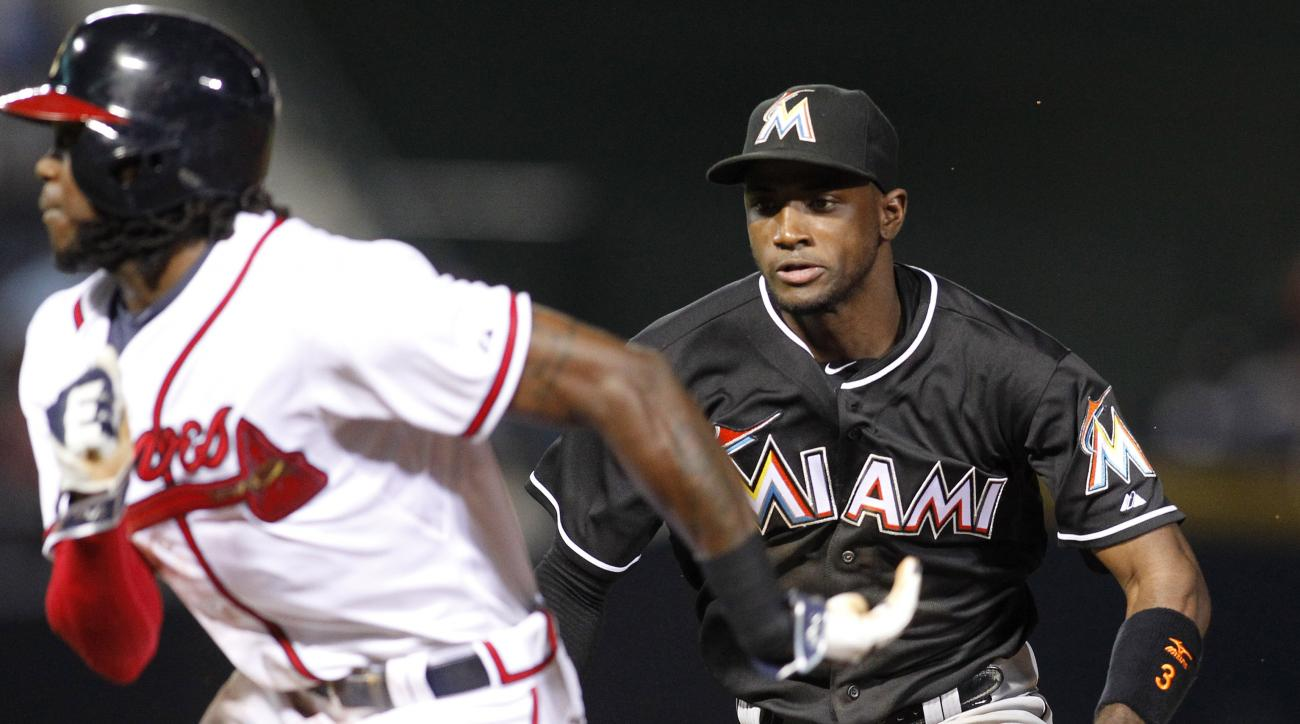 Atlanta Braves' Cameron Maybin is tagged out by Miami Marlins shortstop Adeiny Hechavarria, right, after being picked off and caught stealing second during the sixth inning of a baseball game, Friday, Aug. 7, 2015, in Atlanta. (AP Photo/Brett Davis)