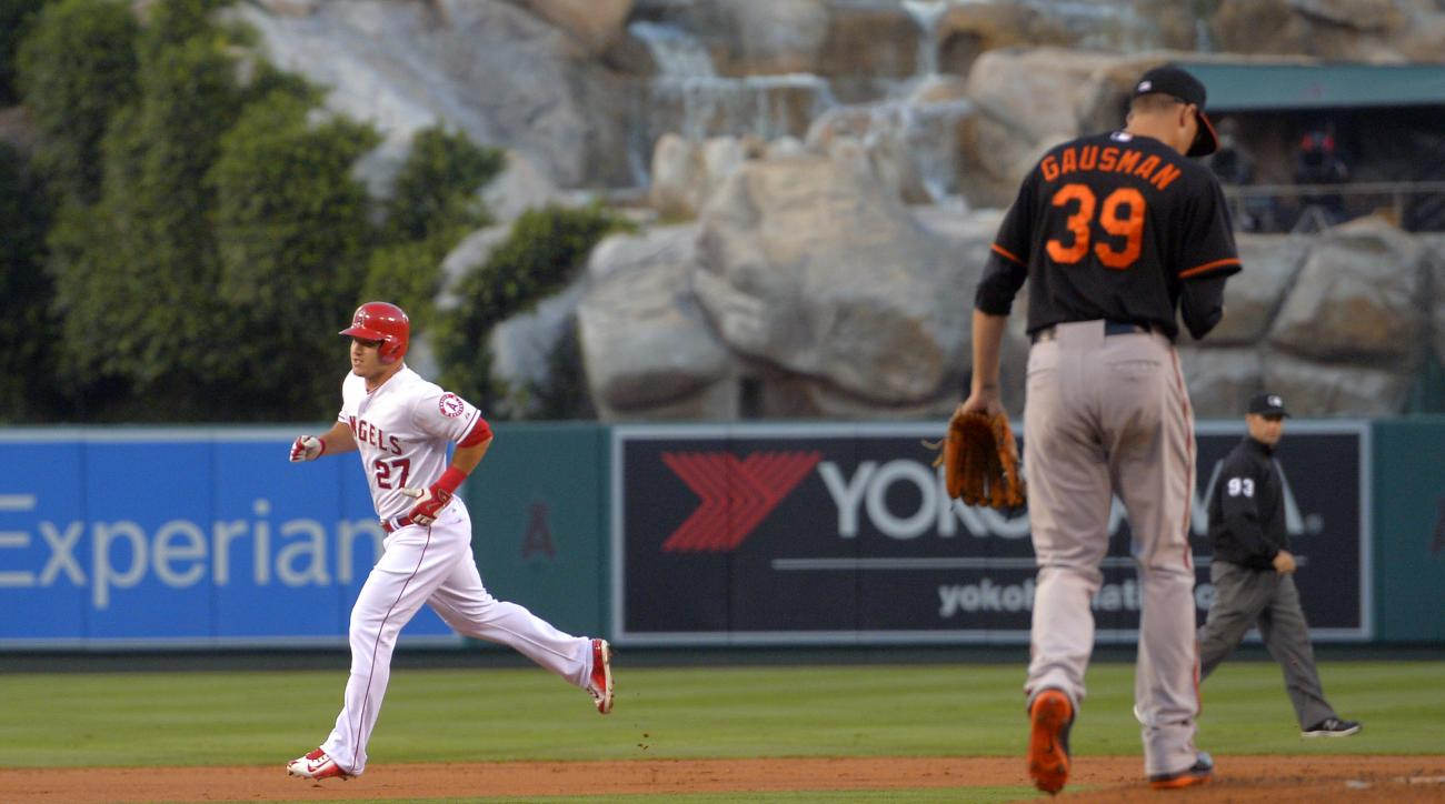 Los Angeles Angels' Mike Trout, left, rounds second after hitting a solo home run as Baltimore Orioles pitcher Kevin Gausman walks back to the mound during the first inning of a baseball game, Friday, Aug. 7, 2015, in Anaheim, Calif. (AP Photo/Mark J. Ter