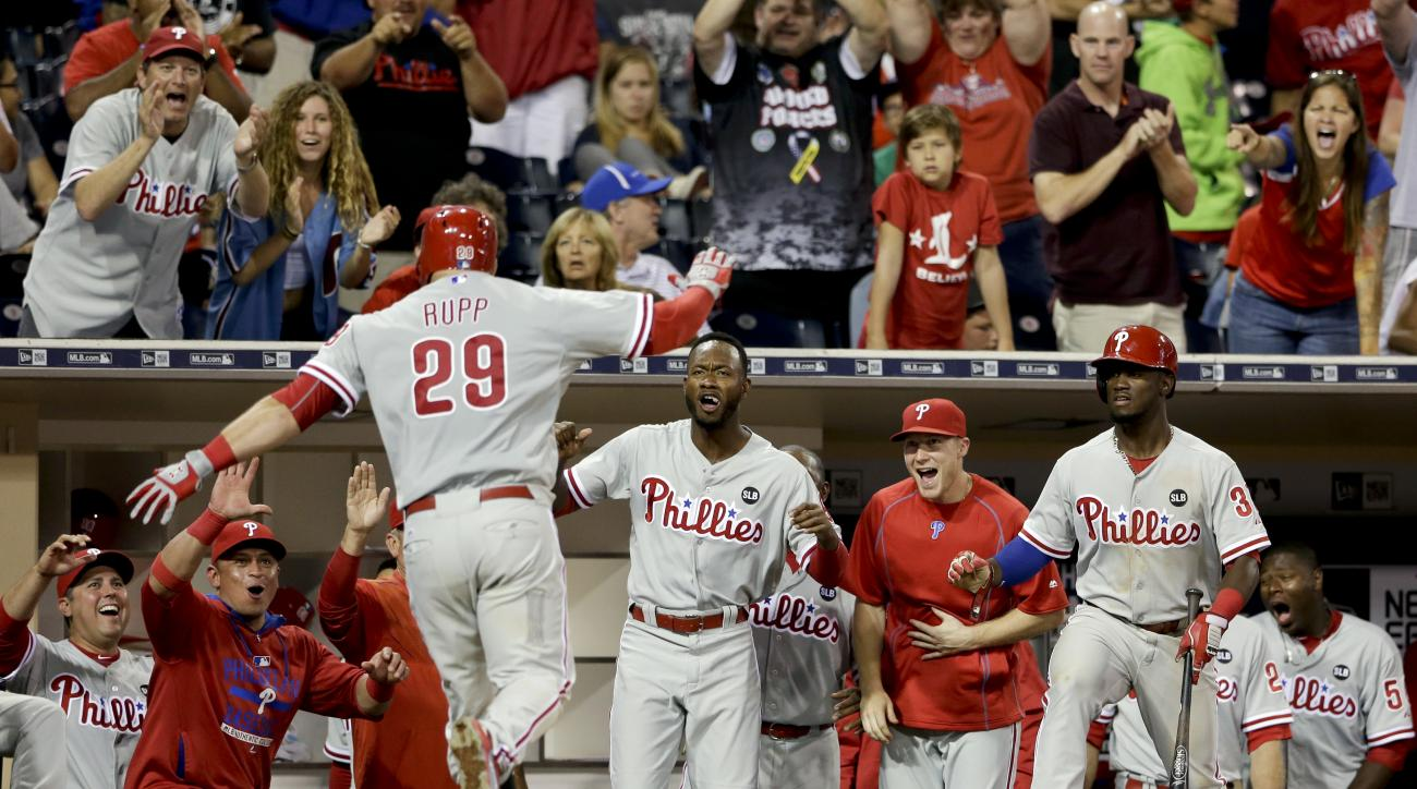 Philadelphia Phillies teammates greet Cameron Rupp (29) after his home run against the San Diego Padres during the twelfth inning of a baseball game Friday, Aug. 7, 2015, in San Diego. (AP Photo/Gregory Bull)