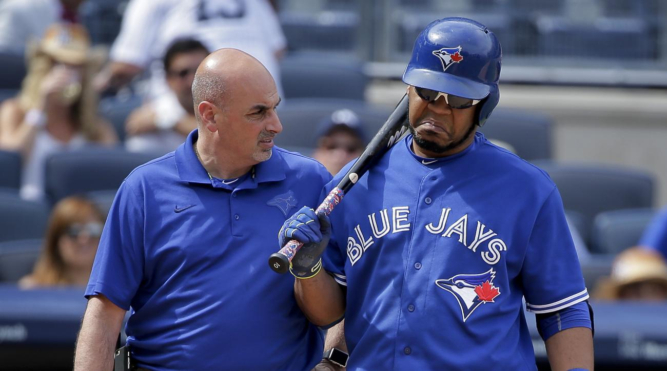 Toronto Blue Jays' Edwin Encarnacion, right, shrugs off questions from a trainer during an at-bat against the New York Yankees during the eighth inning of a baseball game, Saturday, Aug. 8, 2015, in New York. (AP Photo/Julie Jacobson)