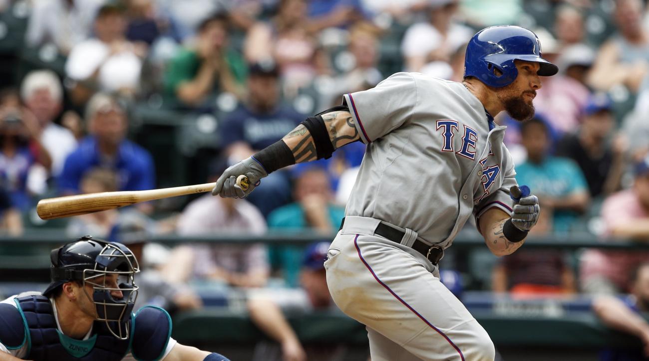 Texas Rangers' Josh Hamilton, right, hits an RBI-single during the eleventh inning of a baseball game against the Seattle Mariners, Saturday, Aug. 8, 2015, in Seattle. Texas defeated Seattle 11-3 in eleven innings. (AP Photo/Joe Nicholson)