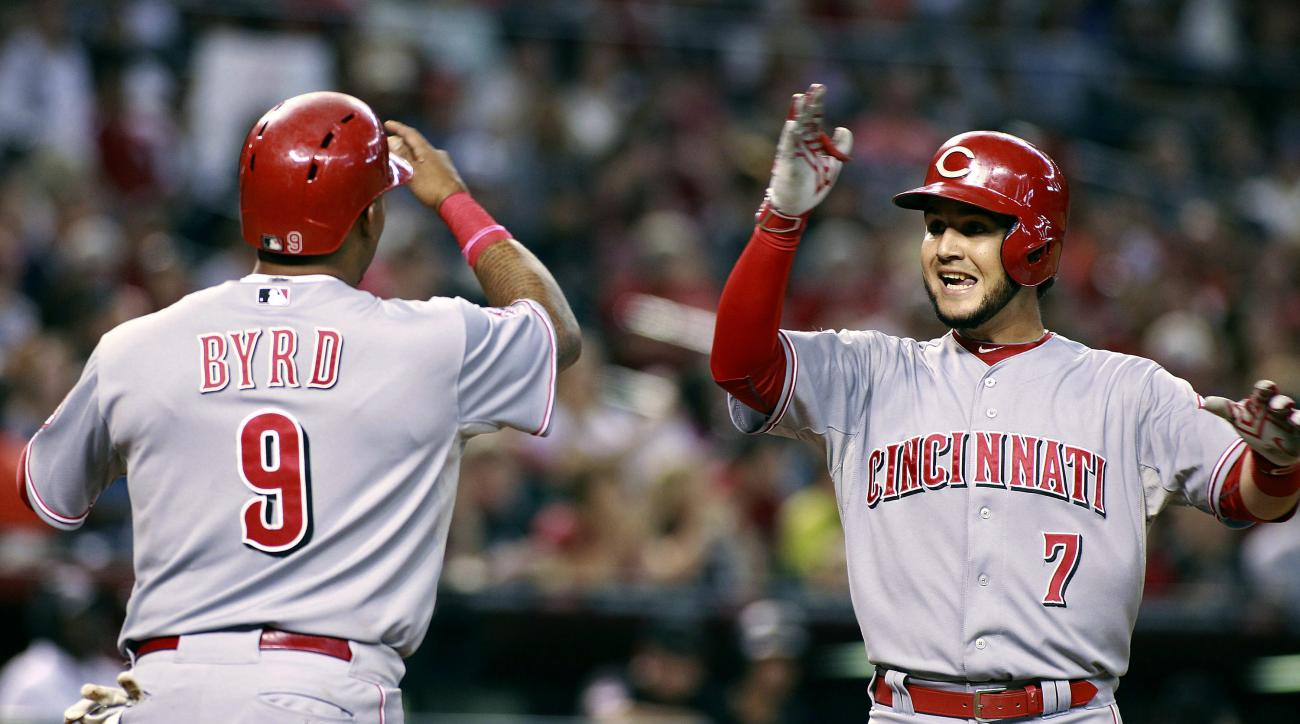 Cincinnati Reds' Eugenio Suarez (7) is congratulated by teammate Marlon Byrd after hitting a two-run home run against the Arizona Diamondbacks during the fourth inning of a baseball game, Saturday, Aug. 8, 2015, in Phoenix. (AP Photo/Ralph Freso)