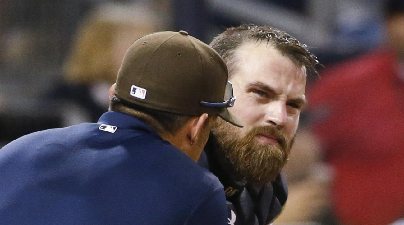 San Diego Padres catcher Derek Norris grimaces as he is examined by a team trainer after being stunned by a foul tip during the eighth inning of a baseball game against the Philadelphia Phillies on Saturday, Aug. 8, 2015, in San Diego. (AP Photo/Lenny Ign