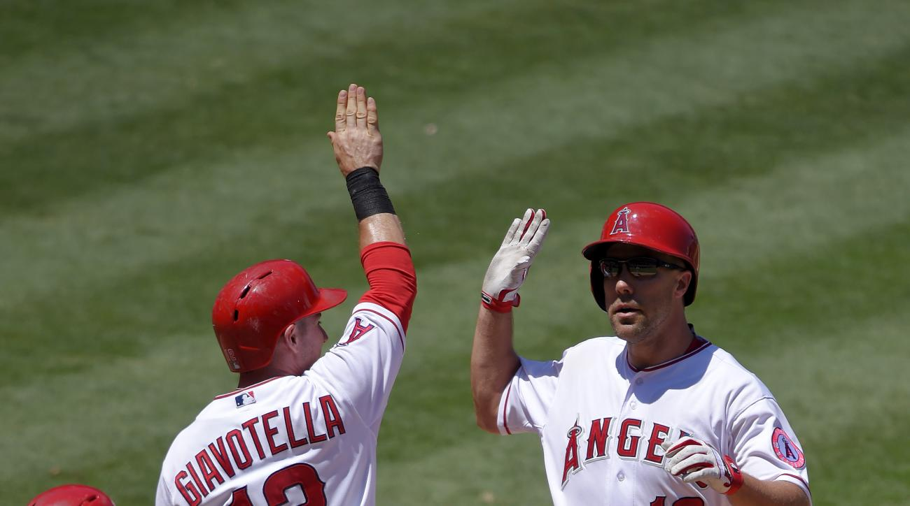 Los Angeles Angels' David Murphy, right, is congratulated by Johnny Giavotella, center, and Kole Calhoun after hitting a three-run home run during the third inning of a baseball game against the Baltimore Orioles, Sunday, Aug. 9, 2015, in Anaheim, Calif.