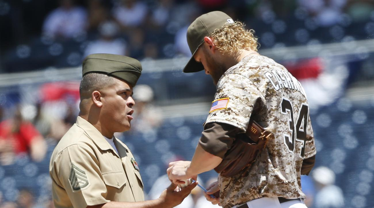 San Diego Padres starting pitcher Andrew Cashner signs a ball for a United States Marine who took the field with the Padres as part of a Wounded Warrior tribute prior to the baseball game against the Philadelphia Phillies, Sunday, Aug. 9, 2015, in San Die