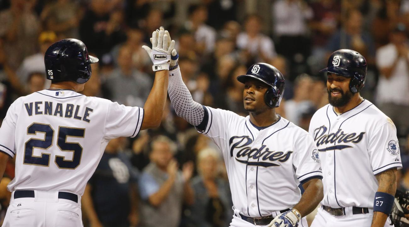 San Diego Padres' Justin Upton high fives with Will Venable  after his two-run homer against the Cincinnati Reds in the fourth inning of a baseball game Monday, Aug. 10, 2015, in San Diego. Matt Kemp, right, was on base at the time. (AP Photo/Lenny Ignelz
