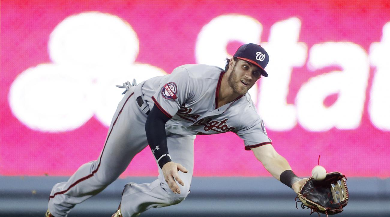Washington Nationals right fielder Bryce Harper dives to catch a ball hit by Los Angeles Dodgers' Enrique Hernandez during the eighth inning of a baseball game, Monday, Aug. 10, 2015, in Los Angeles. (AP Photo/Danny Moloshok)