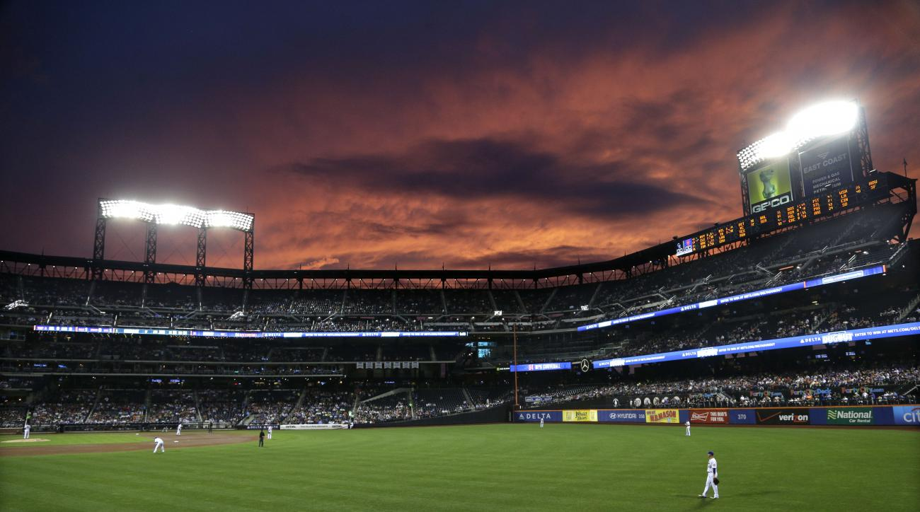 New York Mets left fielder Michael Cuddyer, right, positions himself for the next batter during the fourth inning of a baseball game against the Colorado Rockies, Tuesday, Aug. 11, 2015, in New York. (AP Photo/Julie Jacobson)