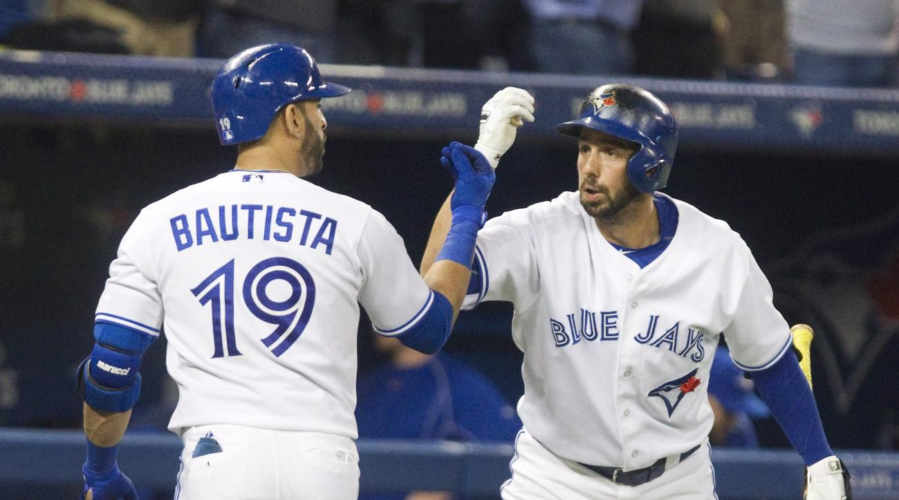 Toronto Blue Jays' Jose Bautista is congratulated by teammate Chris Colabello after he hit a solo home run against the Oakland Athletics during the fifth inning of a baseball game Tuesday, Aug. 11, 2015, in Toronto. (Fred Thornhill/The Canadian Press via
