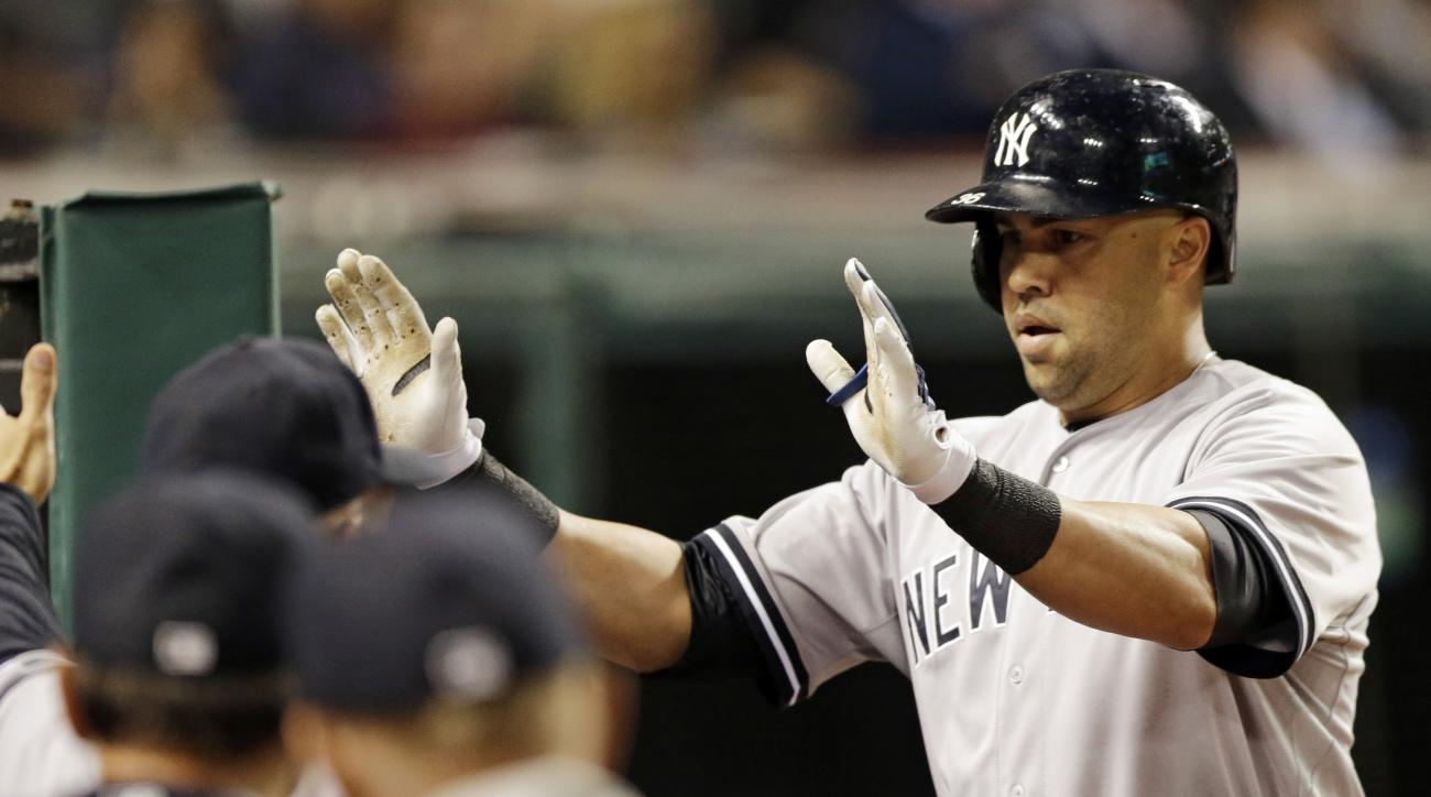 New York Yankees' Carlos Beltran is congratulated by teammates after hitting a solo home run off Cleveland Indians starting pitcher Carlos Carrasco in the eighth inning of a baseball game, Tuesday, Aug. 11, 2015, in Cleveland. (AP Photo/Tony Dejak)