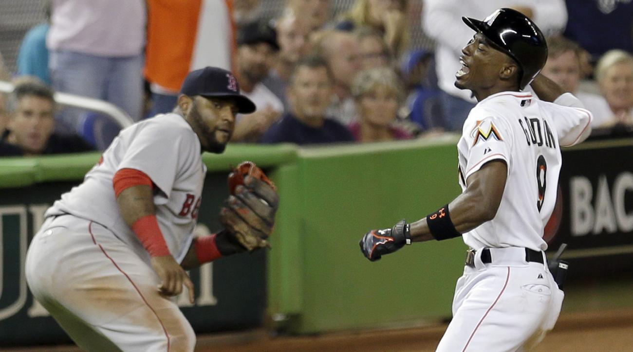 Miami Marlins' Dee Gordon (9) celebrates after batting a triple as Boston Red Sox third baseman Pablo Sandoval, left, looks on in the 10th inning of a baseball game, Tuesday, Aug. 11, 2015, in Miami. The Marlins won 5-4. (AP Photo/Alan Diaz)