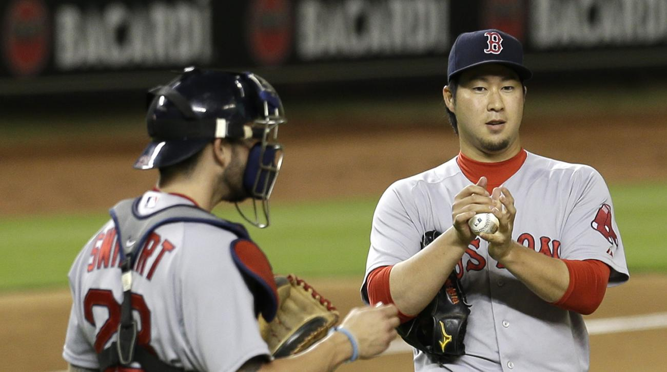 Boston Red Sox's Junichi Tazawa, rubs the ball as catcher Blake Swihart (23) heads to the mound to talk to Tazawa in the ninth inning of a baseball game, Tuesday, Aug. 11, 2015, in Miami. The Marlins won 5-4. (AP Photo/Alan Diaz)
