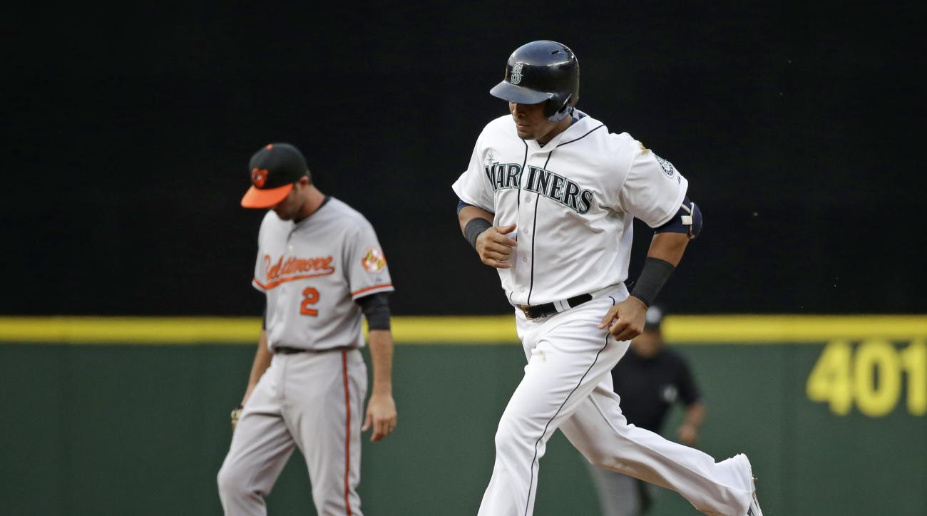 Seattle Mariners' Nelson Cruz, right, rounds the bases on a home run past Baltimore Orioles shortstop J.J. Hardy in the first inning of a baseball game, Tuesday, Aug. 11, 2015, in Seattle. (AP Photo/Elaine Thompson)