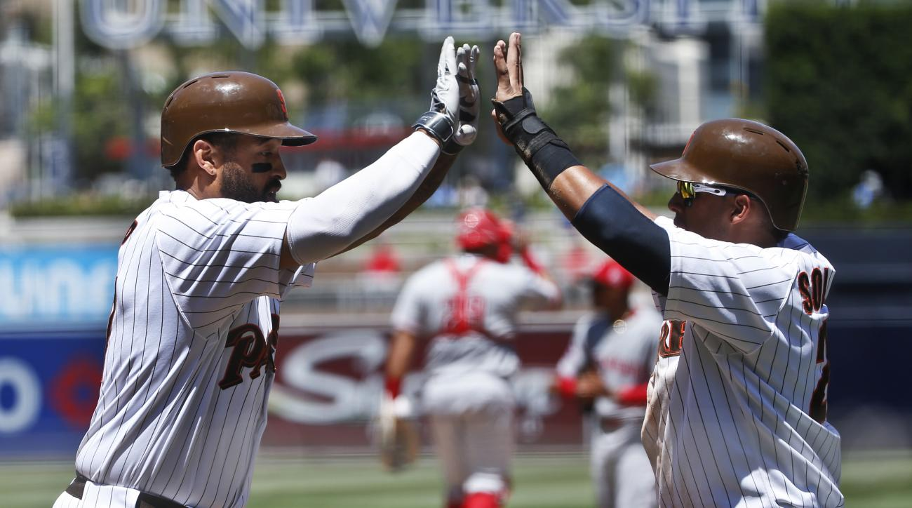 San Diego Padres' Matt Kemp, left, is congratulated by Yangervis Solarte after hitting a three-run home run against the Cincinnati Reds during the first inning of a baseball game Wednesday, Aug. 12, 2015, in San Diego. (AP Photo/Lenny Ignelzi)