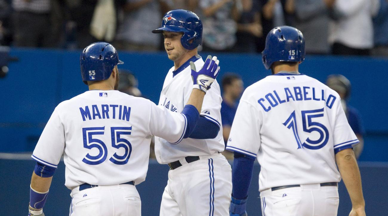 Toronto Blue Jays' Justin Smoak is congratulated by teammate Russell Martin after he hit a three-run home run during the second inning against the Oakland Athletics in a baseball game in Toronto on Wednesday, Aug. 12, 2015. (Fred Thornhill/The Canadian Pr