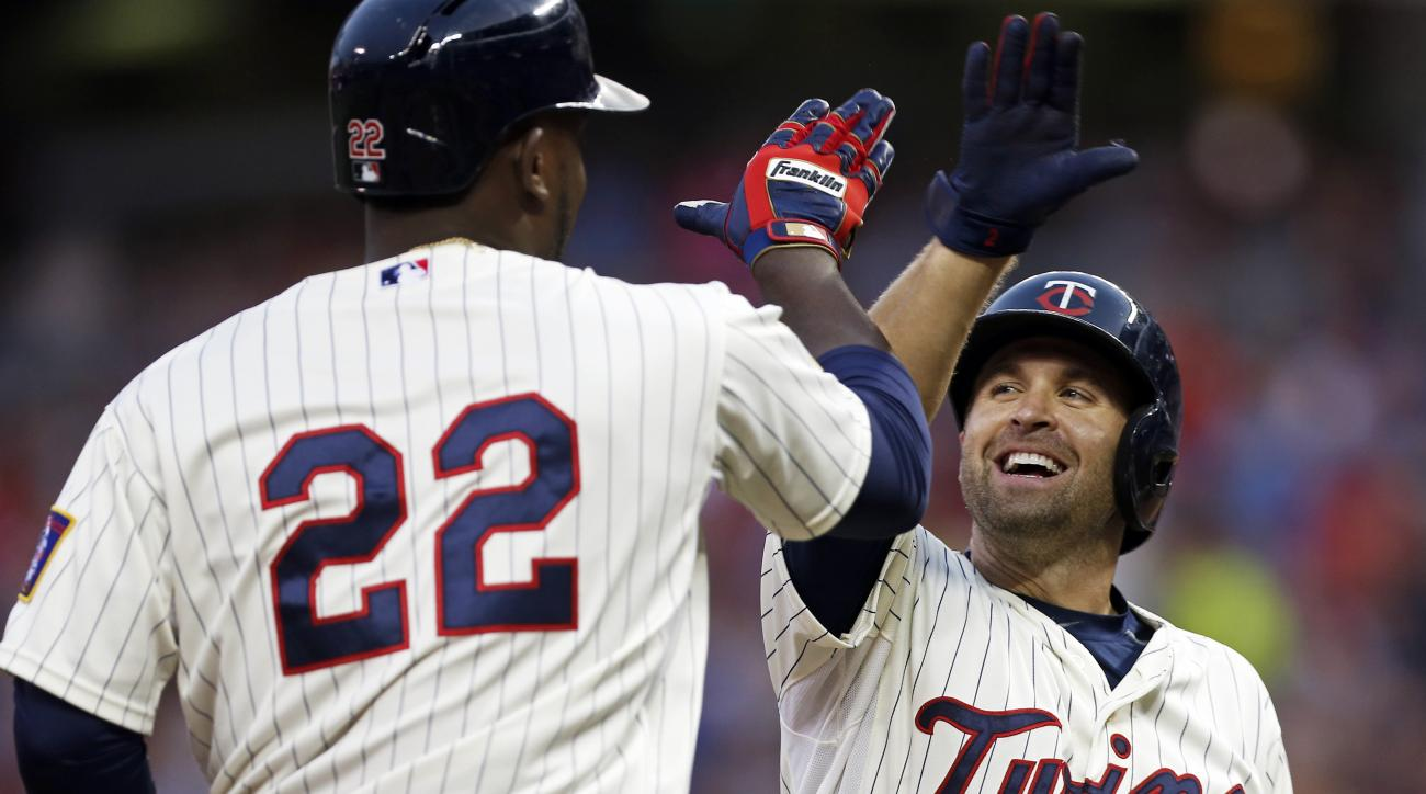 Minnesota Twins' Miguel Sano, left, is congratulated by Brian Dozier after Sano's two-run home run off Texas Rangers pitcher Nick Martinez during the third inning of a baseball game, Wednesday, Aug. 12, 2015, in Minneapolis. (AP Photo/Jim Mone)